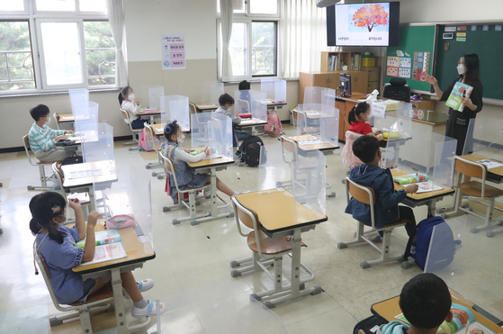First graders at Wonil Elementary School in Suwon, Gyeonggi, return to their classroom Monday for the first time in nearly a month. Wonil was among some 7,000 schools in the greater Seoul area that were allowed to reopen Monday. [YONHAP]