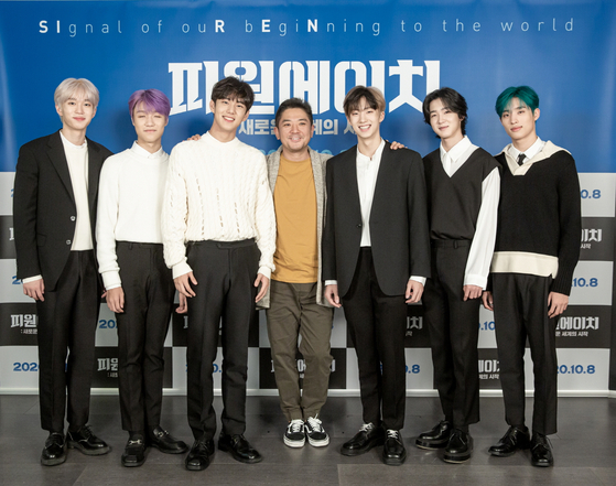 Chang Gamdok, center, poses with members of P1Harmony on Tuesday prior to the online press conference. The members of P1Harmony are, from left: Theo, Jongseob, Intak, Jiung, Soul and Keeho. [FNC ENTERTAINMENT]