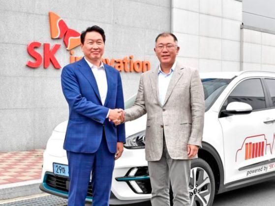 SK Chairman Chey Tae-won, left, and Hyundai Motor Group Executive Vice Chairman Euisun Chung shake hands at SK Innovation's factory in Osan, South Chungcheong, in July. [HYUNDAI MOTOR]