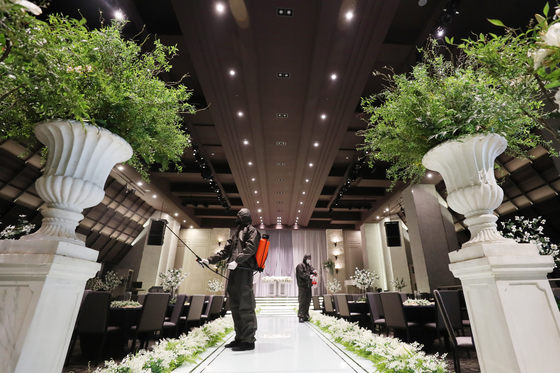 Employees disinfect a wedding hall in Suwon, Gyeonggi, on Aug. 19. Korea's number of marriages sharply declined in July due to the prolonged Covid-19 pandemic. [NEWS1]