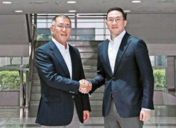 Hyundai Motor Group Executive Vice Chairman Euisun Chung, left, shakes hands with LG Chairman Koo Kwang-mo at LG Chem's factory in Ochang, North Chungcheong, in June. [HYUNDAI MOTOR]