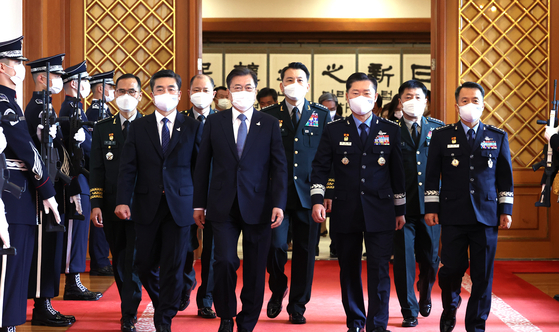 President Moon Jae-in, fourth from left, walks with Defense Minister Suh Wook, second from left, and newly promoted military generals following an appointment ceremony at the Blue House in Seoul on Wednesday. [YONHAP]