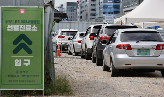 Cars line up at a drive-thru Covid-19 testing center at the Ewha University Seoul Hospital in Gangseo District, western Seoul, as new coronavirus cases jumped to over 100 again Wednesday. [YONHAP]