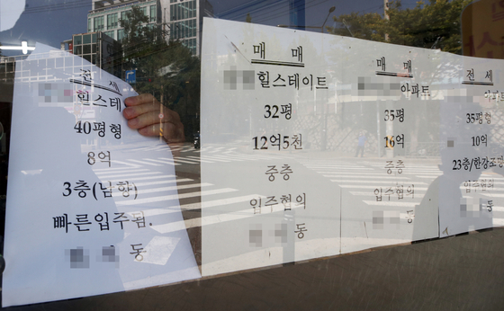 A jeonse offering post being taken down at a real estate agency in Mapo District, western Seoul, on Tuesday. Jeonse offerings have been drying up fast, especially in Gangnam District, southern Seoul, since the National Assembly passed legislation that protects tenants, including automatic extension and a cap on rent increases. [YONHAP]