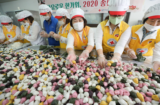 At the Nowon branch of the Korean Red Cross in Seoul on Wednesday, volunteer workers make songpyeon, or half moon-shaped stuffed rice cakes, which will be handed out to those in need for the coming Chuseok holiday, or Korean harvest festival. [NEWS1]