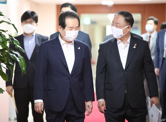 Prime Minister Chung Sye-kyun, left, and Finance Minister Hong Nam-ki walk into a cabinet meeting at the government complex in central Seoul on Wednesday. The National Assembly approved a 7.8 trillion won ($6.9 billion) fourth supplementary budget late Tuesday. [YONHAP]