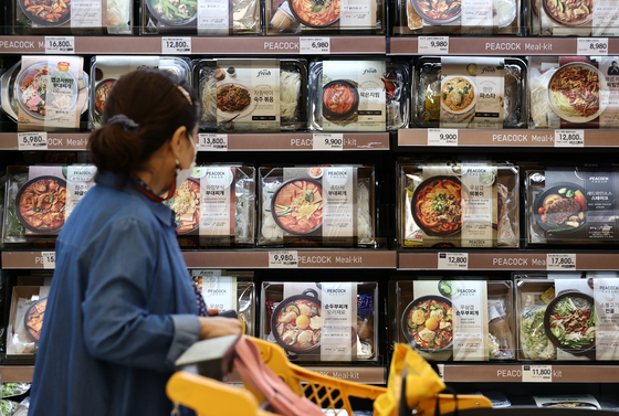 A customer examines meal kits on the shelves of a discount store in Seoul, Wednesday. Meal kits are becoming popular with a growing number of people who opt to cook at home rather than eat out. Sales of kits shot up 238.8 percent on year in September, according to local retail chain Emart. [YONHAP]