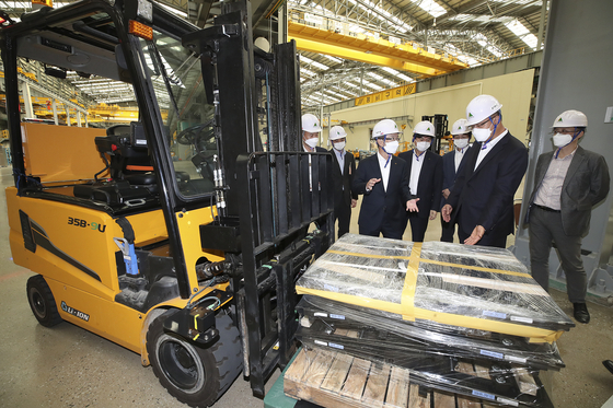 KT and Hyundai Construction Equipment executives watch the demonstration of a 5G-connected, unmanned forklift at Hyundai's factory in Gunsan, North Jeolla, on Thursday. The forklift can drive on its own, understand commands and be remotely controlled via 5G and augmented reality (AR) glasses. The forklift truck is the first outcome of a partnership signed between the two in May to develop smart industrial vehicles and machinery. [KT, HYUNDAI CONSTRUCTION EQUIPMENT]