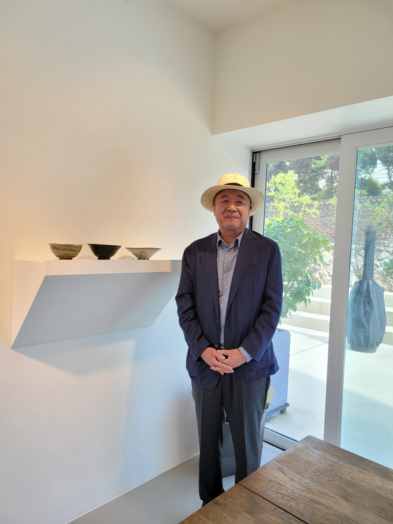 Ceramic artist Kwon Dae-sup stands by his bowls at Park Ryu Sook Gallery in Seoul on Wednesday.[MOON SO-YOUNG]