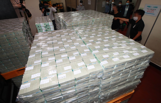 Workers from the note-issuing bureau of the Bank of Korea in Gangnam District, southern Seoul, on Thursday unload brand-new bank notes to be circulated in commercial banks for the coming Chuseok harvest holidays. [JOINT PRESS CORPS]