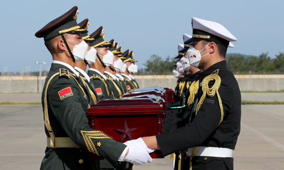 South Korean honor guards hand over caskets to Chinese guards at a ceremony at Incheon International Airport on Sunday. The caskets contain 117 sets of remains of Chinese soldiers killed during the 1950-53 Korean War. It was the seventh such repatriation ceremony. Of the remains repatriated Sunday, 103 sets were excavated last year from Arrowhead Ridge, a battle site inside the demilitarized zone separating the two Koreas. Others were uncovered in other parts of South Korea. Since the two countries agreed on the return of the Chinese troop remains in 2014 in a gesture of their friendship, Seoul has returned 716 sets of remains of Chinese soldiers, including the latest 117 sets.  [MINISTRY OF NATIONAL DEFENSE]