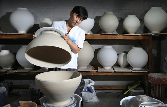 Ceramic artist Shin Chul assembles the upper part of a moon jar with the lower part at his ceramic studio Huguro-Bitzun-Dal, located in Icheon, Gyeonggi. [BY PARK SANG-MOON]