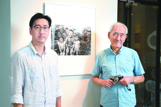 Lim June-young, left, and his father Lim Chung-eui pose at Leica store in Cheongdam-dong, southern Seoul, where the photo exhibition of their grandfather and father Lim In-sik and June-young, is being held until Oct. 4. [WOO SANG-JO]