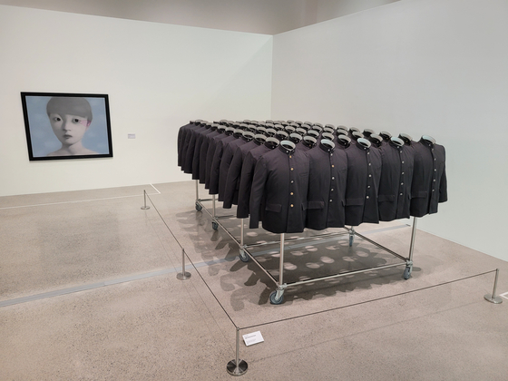 """Korean artist Do Ho Suh's installation work 'High School Uni-Form"""" juxtaposed with Chinese artist Zhang Xiaogang's painting 'Amnesia and Memory No.16"""" as part of Space K Seoul's inaugural exhibition 'Distorted Portrait."""" [MOON SO-YOUNG]"""