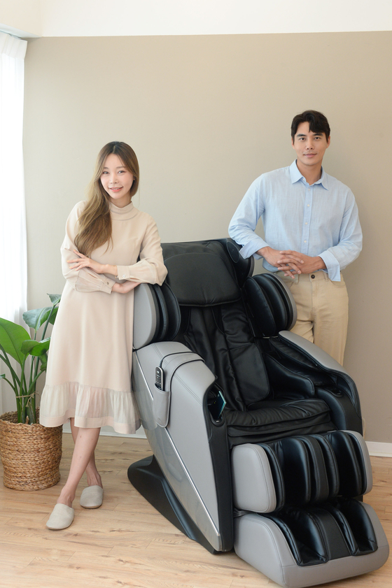 "Two models pose next to LG Electronics' new premium massage chair ""Healing Me Maldive,"" released Monday. According to the company, the massage chair can recognize the user's voice and change its length to fit the height of the user. The chair is priced at 4.4 million won ($3,800). [LG ELECTRONICS]"