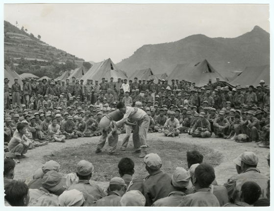 A game of ssireum (traditional Korean wrestling) set up by the ICRC at the prison camp on Geoje Island, one of the largest prison camps during the Korean War, in June 1951. [ICRC]