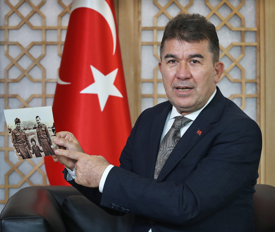 Ambassador of Turkey to Korea, Ersin Ercin, speaks with the Korea JoongAng Daily at the Embassy of Turkey in central Seoul on July 16. He is holding up a photo of Lieutenant Mehmet Gonenc and other soldier with a young Korean girl they found among the ruins of the war. [PARK SANG-MOON]