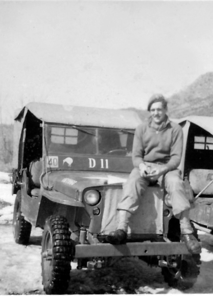 """Des Vinten sitting on the bonnet of his jeep. """"The 40 on the windscreen was the Tac Sign for 1 Britcom Divisional Signal Regiment, the Kiwi says I am a Kiwi dispatch rider and the vehicle number D11 tells every one I am a dispatch rider and should not be delayed when on the road,"""" he said. [DES VINTEN]"""
