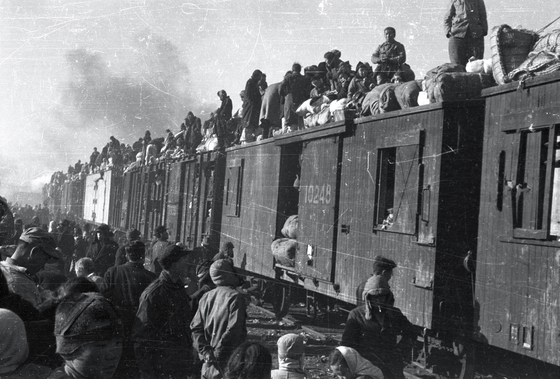War refugees traveling on top of the train in Daegu on Dec. 29, 1950. [ICRC/JACQUES DE REYNIER]