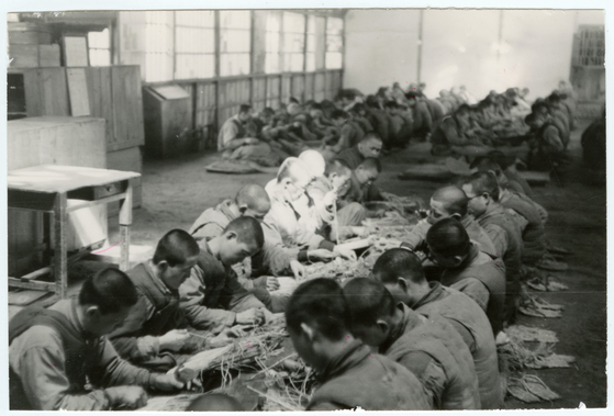 Prisoners of war in a camp in Busan weaving baskets on March 14, 1951. [ICRC/JACQUES DE REYNIER]