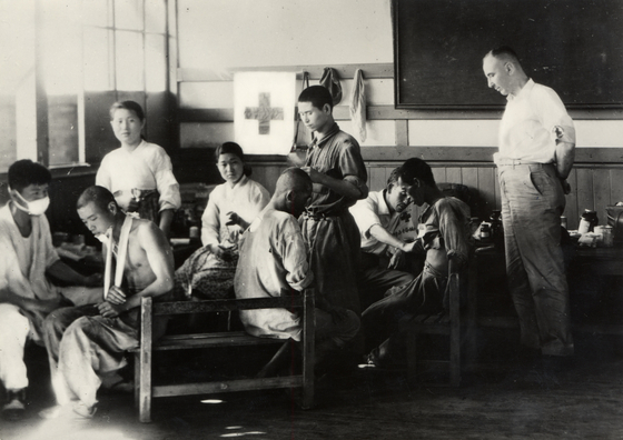 Medical staff members tending to the wounded at prison camp No. 100 in Korea, which had 245 prisoners of war, on July 26, 1950. On the far right is ICRC delegate Frederick Bieri. [ICRC]