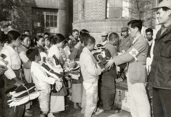 KNRC employee Hwang Nahm-yong supervises the distribution of relief goods to refugees at an elementary school in Seoul on Nov. 2, 1950. [ICRC]