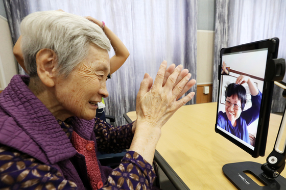 An elderly woman at a nursing home in Suwon, Gyeonggi, holds a video call with her daughter Tuesday ahead of Chuseok instead of an in-person visit, following with Covid-19 social distancing guidelines. [NEWS1]
