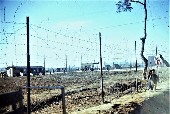 Korean orphans running along the fence of the K-55 air base, where South African forces were stationed, in a photo taken by Sgt. Louw. [SOUTH AFRICAN KOREAN WAR VETERANS ASSOCIATION]