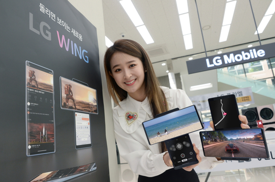 "A model holds up LG Electronics' ""swiveling"" Wing smartphone. [LG ELECTRONICS]"