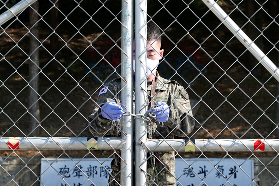 A masked soldier locks the front gate of a Korean Army unit in Pocheon, Gyeonggi, on Monday after 36 Covid-19 cases were confirmed there. [YONHAP]