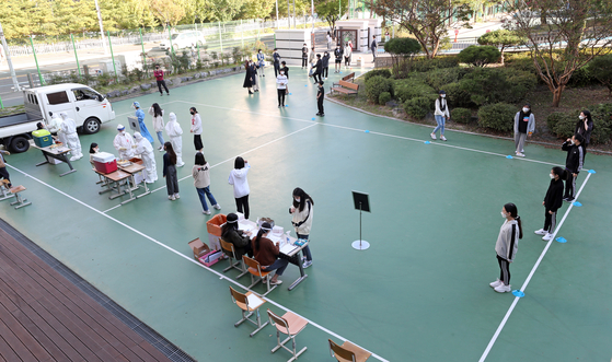 Students at a middle school in Daejeon receive testing for the coronavirus Tuesday on the school's basketball court after a seventh grader tested positive Monday. [YONHAP]