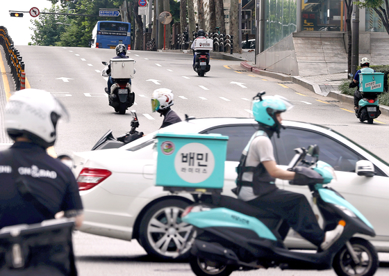 Delivery workers on motorcycles deliver food in Seoul, where online orders have sharply increased since the coronavirus outbreak began. [YONHAP]