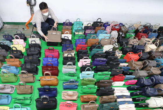 An employee shows confiscated knockoff luxury handbags at the Seoul Main Customs building in Gangnam District, southern Seoul. Seoul Main Customs announced on Wednesday that it caught a pair of siblings illegally distributing 29 billion won ($25 million) of fake merchandise and sent the case to the prosecution. [YONHAP]