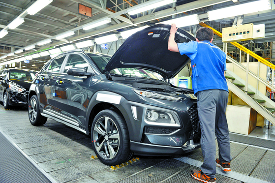 An employee at Hyundai Motor's Ulsan 1 Plant looks inside a Kona vehicle at the production line.[HYUNDAI MOTOR]