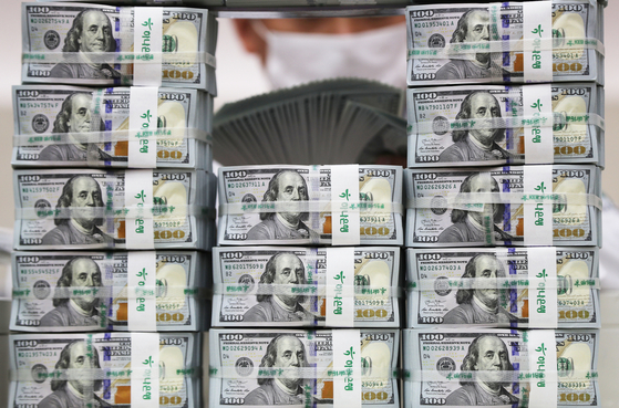 An employee poses with stacks of dollar bills at a Hana Bank branch in Jung District, central Seoul, on Wednesday. According to data from the Bank of Korea, foreign exchange reserves came to $420.55 billion as of the end of September, up $1.59 billion from a month earlier. [YONHAP]