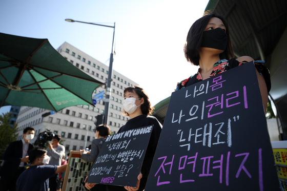 Protesters demand a complete lifting of a ban on abortions outside the National Assembly on Wednesday. Earlier in the morning, the government proposed to partially lift the ban. [YONHAP]