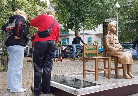 "People look at a ""comfort woman"" statue, symbolizing Korean victims of wartime sexual slavery by the imperial Japanese army during World War II, erected in Berlin, Germany, on Sept. 27. [YONHAP]"