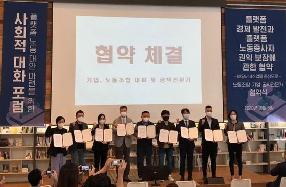 Speakers hold up a written agreement signed Tuesday at a forum to protect delivery workers held in Jung District, central Seoul. [PARK MIN-JE]