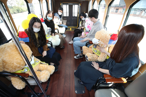 Stuffed dolls are placed on every other seat of a tour bus in Daegu Wednesday to guarantee social distancing among passengers. [YONHAP]