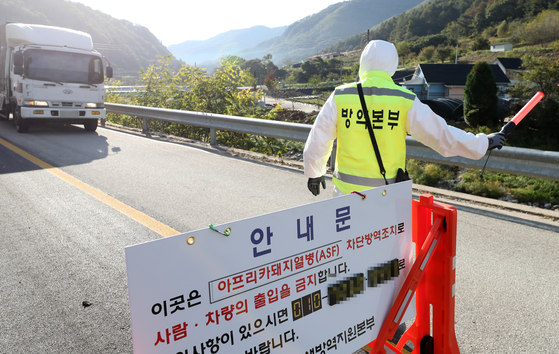 A government official blocks the entrance to a pig farm in Hwacheon County, Gangwon, after pigs supplied from this region were found infected by African swine fever on Friday. [YONHAP]