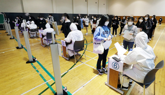 Students undergo body temperature checks before testing for an exam at Sungshin Women's University in central Seoul on Sunday. [YONHAP]