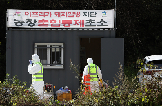 Quarantine workers restrict entry into a farm confirmed to be infected with African swine fever in Hwacheon,Gangwon on Sunday. [YONHAP]