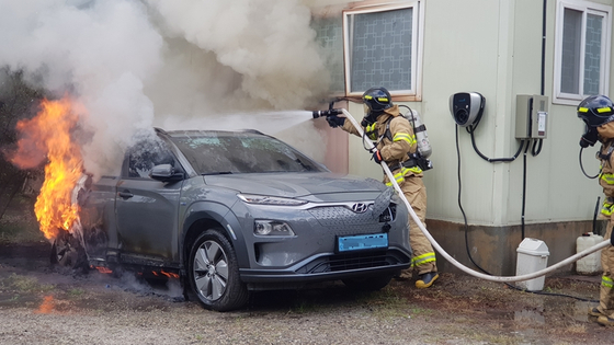 Firefighters douse flames erupting from a Hyundai Kona electric vehicle that burst into flames last July near an office in Gangneung, Gangwon. [GANGNEUNG FIRE DEPARTMENT]