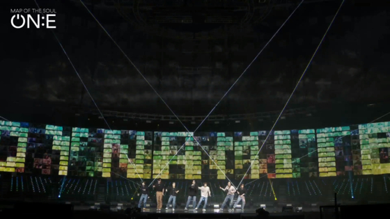 """BTS performs its latest hit """"Dynamite"""" against an LED screen with fans' faces during its second online concert 'BTS Map of the Soul ON:E"""" held on Saturday. [BIG HIT ENTERTAINMENT]"""