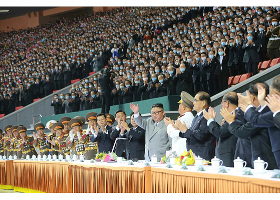North Korean leader Kim Jong-un, center, waves at mass games organized on Sunday to commemorate the ruling Workers' Party's 75th anniversary. [NEWS1]