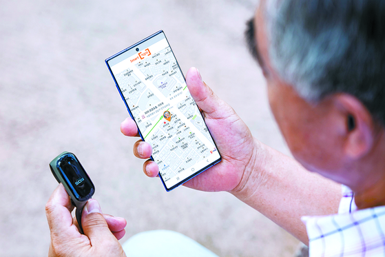 A senior citizen looks at his smartphone for location information. [YONHAP]