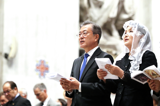 In this file photo, President Moon Jae-in and his wife Kim Jung-sook sing during a special mass for the Korean Peninsula's peace at the St. Peter's Basilica in the Vatican on Oct. 18, 2018. Moon later donated the tie to the 2018 WeAJa charity market.  [YONHAP]