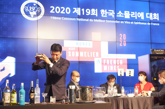 A bartender shakes up a cocktail on stage during the final round of the 19th Korea Best Sommelier in French Wines Competition held at the JW Marriott in Jongno District, central Seoul, on Tuesday. [SOPEXA KOREA]