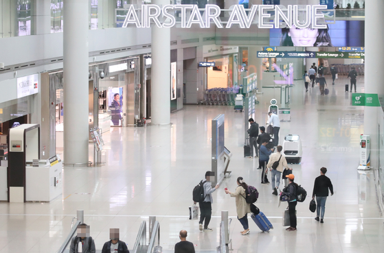 Customers walk around the departure terminal where duty-free stores are located at Incheon International Airport on Tuesday. The government held a third round of bidding for duty-free business licensing at the airport's Terminal 1, but failed to attract interested parties. Only one mid-size company bid for six units covering 6,131 square meters (66,000 square feet). [YONHAP]
