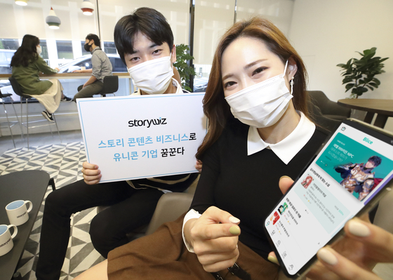 Models hold up a mobile phone with the app for Blice on Tuesday, prior to the press conference held at Gwanghwamun, central Seoul. Blice is a web novel platform run by Storywiz. [KT]